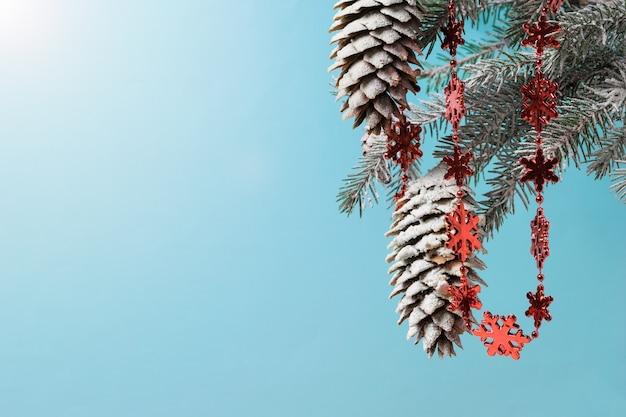 Branche d'épinette avec des cônes au soleil, décorée d'une guirlande. préparer noël