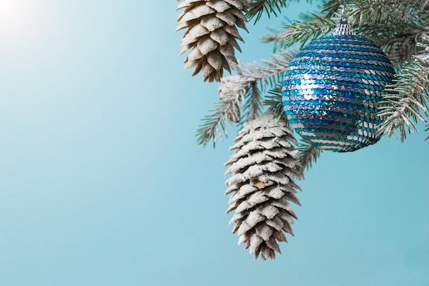 Une branche d'épinette avec des cônes dans la neige et une boule brillante