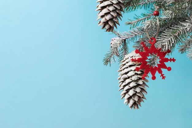 Branche d'épinette dans la neige et décoration de flocons de neige rouges. préparer noël