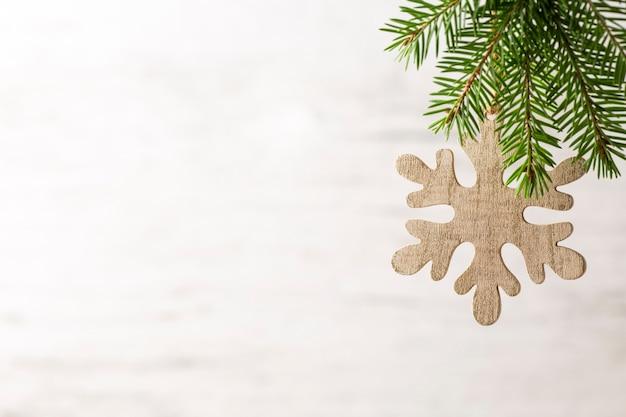 Branche d'épinette avec des décorations de noël sur fond gris.