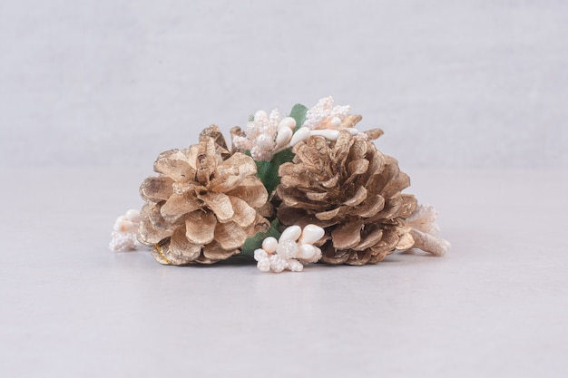Branche d'épinette enneigée avec des cônes de sapin isolés sur blanc.
