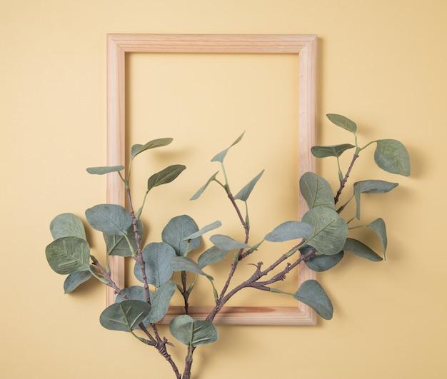 Branche d'eucalyptus et cadre en bois sur fond jaune. vue de dessus et espace de copie