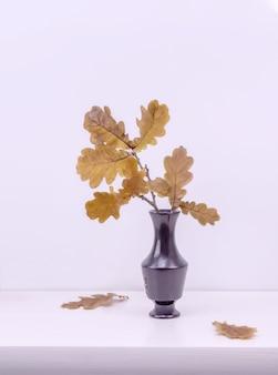 La branche avec des feuilles d'automne sèches est dans un vase sur la table