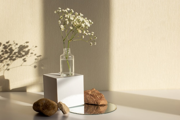 Une branche d'une fleur de gypsophile debout sur un cube de papier blanc et des pierres