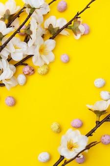 Branche de fleurs blanches sur fond jaune avec des bonbons, des œufs en chocolat de pâques. maquette de pâques. fond de printemps minimaliste.