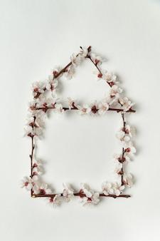 Branche avec des fleurs blanches en forme de maison sur fond blanc.