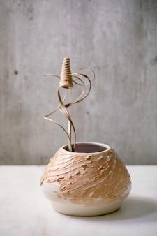 Branche de fleurs et de brindilles sèches dans un vase en céramique beige sur une table en marbre blanc avec un mur gris derrière. copiez l'espace.