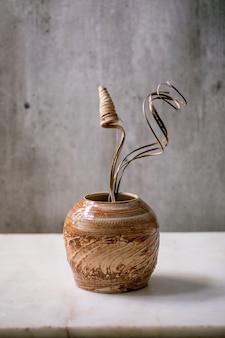 Branche de fleurs et de brindilles sèches dans un vase en céramique marron sur une table en marbre blanc avec un mur gris derrière. copiez l'espace.