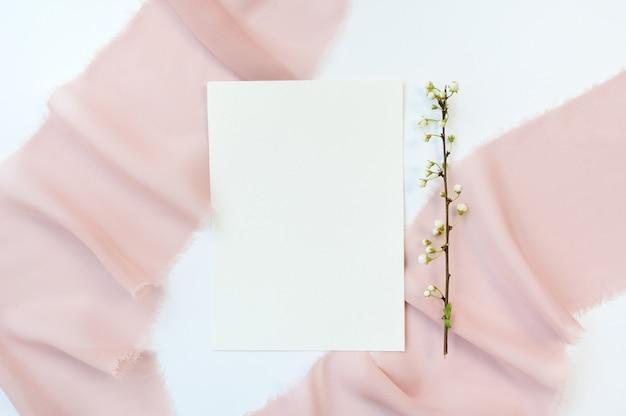 Branche de fleurs de cerisier blanc sur textile beige satiné