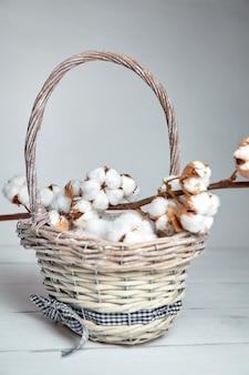 Branche de fleurs de coton moelleux et un panier en osier sur une table en bois blanc