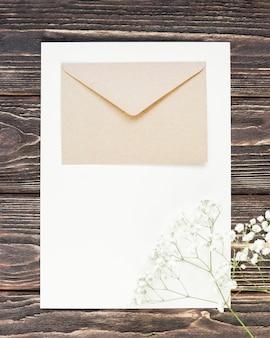 Branche de fleurs épanouies à côté de la carte de mariage