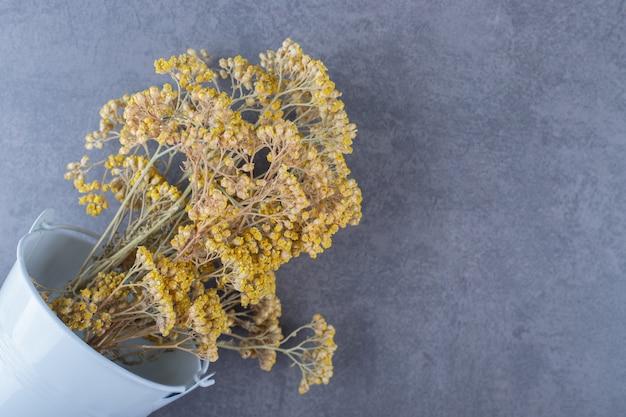 Branche de fleurs séchées dans un seau