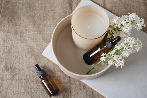 Une branche de lilas blanc, une bougie aromatique dans un verre et des bouteilles brunes avec de l'huile aromatique dans un bol en céramique sur un espace de copie de fond en lin naturel