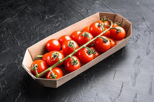Branche mûre de tomates cerises, dans un récipient, sur fond noir en pierre
