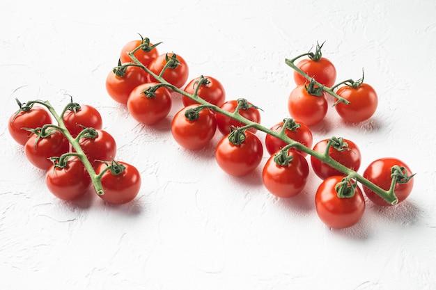 Branche mûre de tomates cerises, sur fond de pierre blanche