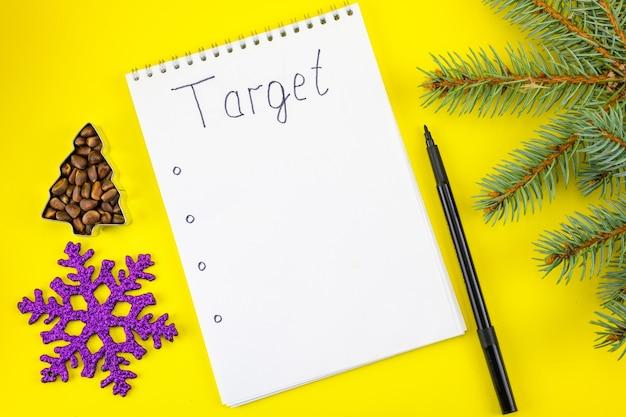 Branche de noël, pin, flocon de neige et cahier avec l'inscription target.