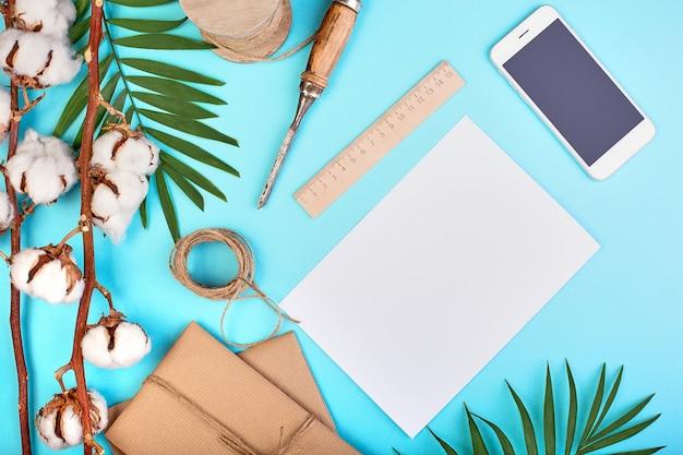 Branche de palmier, coffrets cadeaux, boules de coton, smartphone et écheveau de corde de jute sur une surface bleue