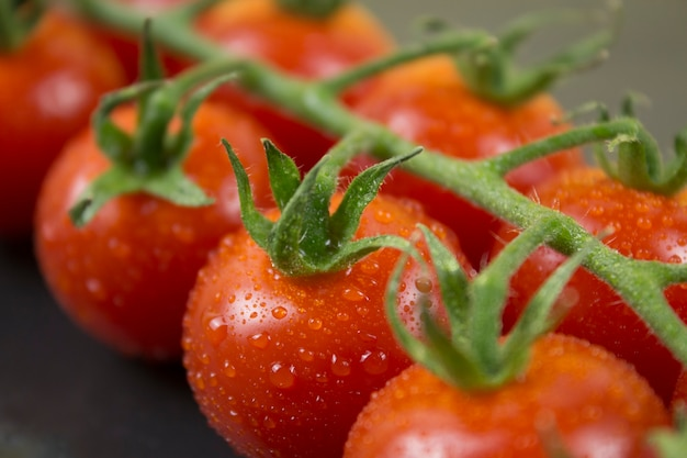 Branche de petites tomates rouges sur fond de pierre noire close up