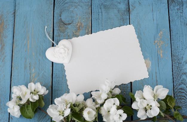 Une branche de pommier en fleurs, un coeur et une feuille de papier vide