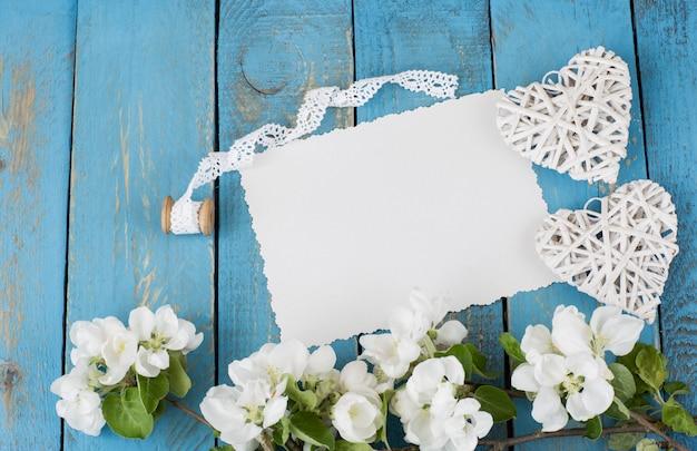 Une branche de pommier en fleurs, deux cœurs, un ruban de dentelle et une feuille de papier vide