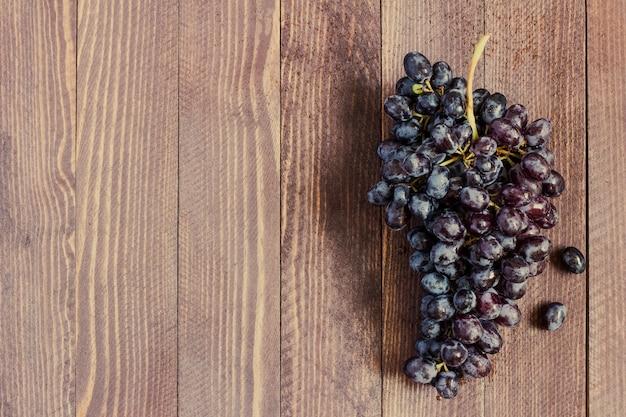 Branche de raisin noir sur bois foncé