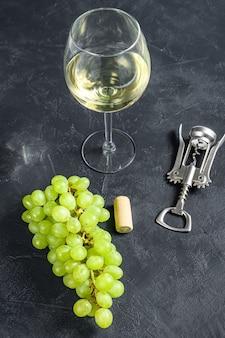 Branche de raisin vert, un verre à vin, un tire-bouchon et un bouchon. concept de vinification. fond noir.