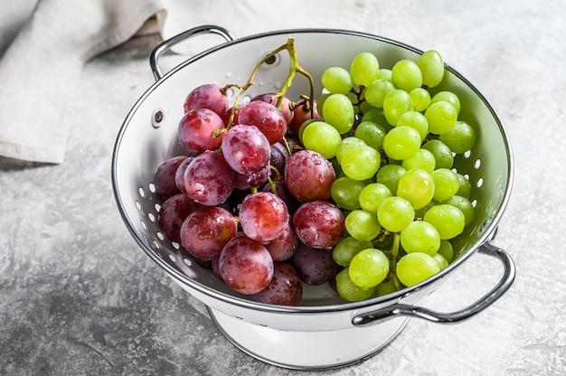 Branche de raisins rouges et verts dans une passoire. fond gris.