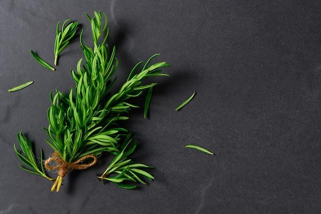 Branche de romarin frais sur fond de tableau noir.