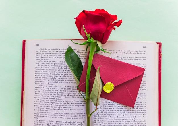 Branche de rose rouge avec enveloppe sur un gros livre