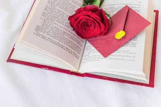Branche de rose rouge et enveloppe sur un livre