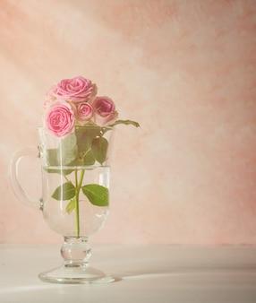 Branche de roses dans un verre