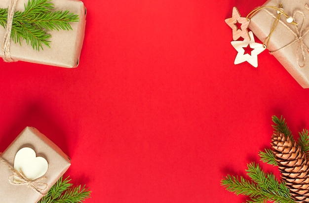 Branche de sapin, boîte-cadeau et jouets d'arbre de noël sur fond rouge. matériaux écologiques