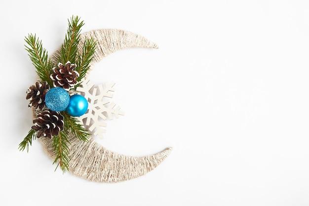 Branche de sapin, boules bleues, pommes de pin sur croissant et flocon de neige.