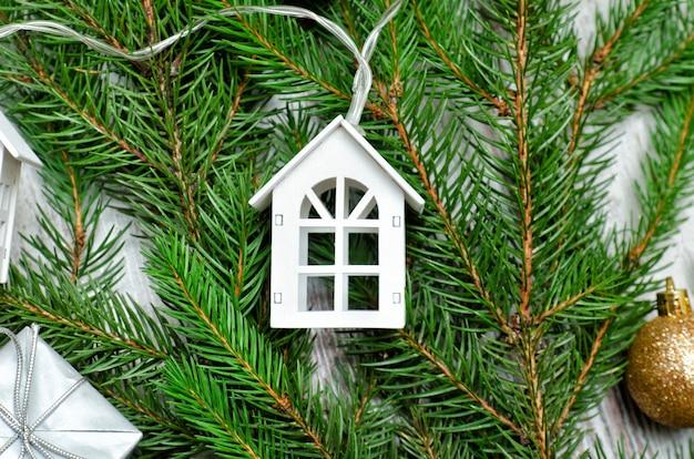 Branche de sapin décorée et petite maison blanche. concept de vacances