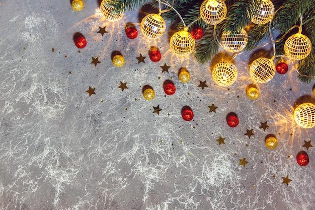 Branche de sapin de noël avec des boules de guirlandes décoratives lumière rougeoyante sur fond gris avec des boules et des étoiles dorées et rouges. mise à plat