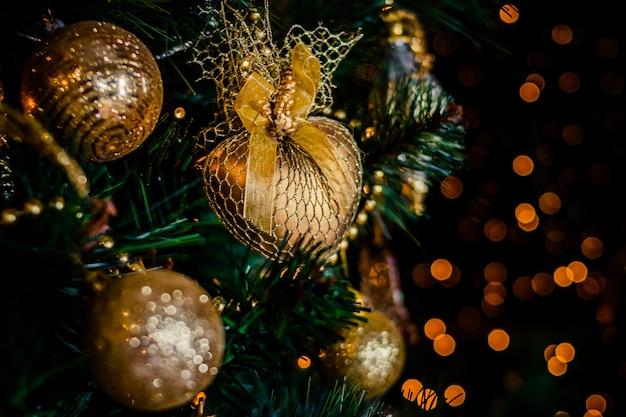 Branche de sapin avec des ornements de noël en or. lumières de fête, scintille. décoration de fête