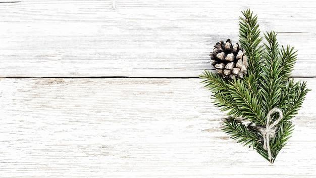 Branche de sapin et pomme de pin sur fond de noël de planche de bois blanc.