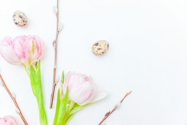 Branche de saule de coton oeufs de pâques et bouquet de fleurs de tulipes fraîches roses sur fond en bois blanc rustique. concept de pâques