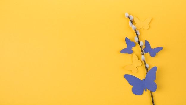 Branche de saule avec des papillons de papier brillant