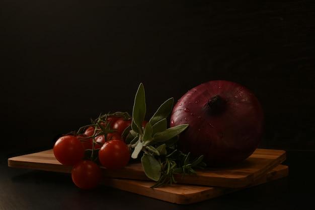 Une branche de tomates cerises mûres, d'oignons et un bouquet de légumes verts frais