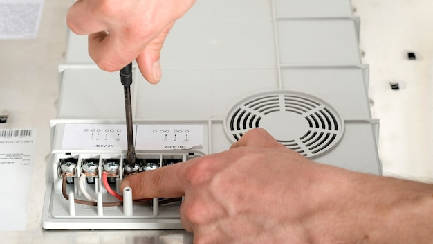 Branchement électrique de la cuisinière à induction, contacts, électricité. électricien, bricoleur, câblage professionnel et installation dans la cuisine.