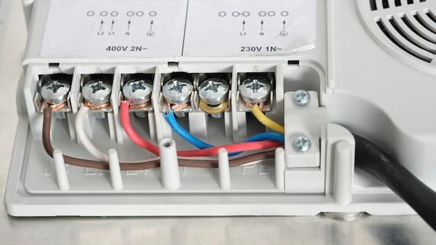 Branchement électrique de la plaque de cuisson à induction, contacts, électricité. câblage professionnel et plaque de cuisson dans la cuisine.