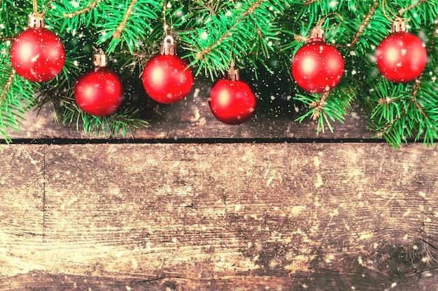 Branches d'un arbre de noël sur de vieilles planches. fond de noël. décorations de noël. fond de nouvel an. fond xmax. image tonique. chute de neige.