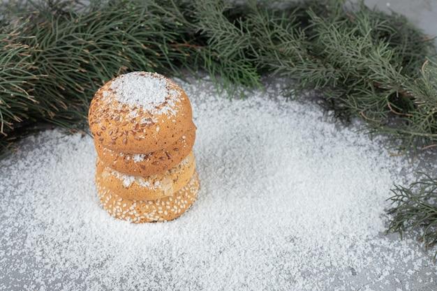 Branches d'arbres derrière une pile de cookies sur une surface en marbre