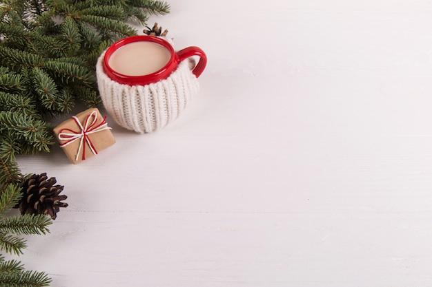 Branches d'arbres de noël, cadeaux et boisson chaude dans une tasse, noël, carte de voeux. fond