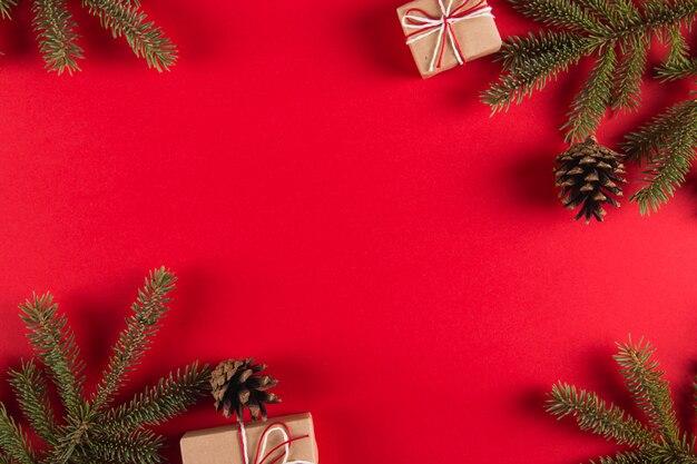 Branches d'arbres de noël, cadeaux et pommes de pin sur un fond rouge, noël, carte de voeux.