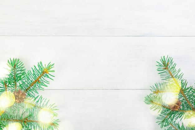 Branches d'arbres de noël avec des cônes sur une planche en bois clair