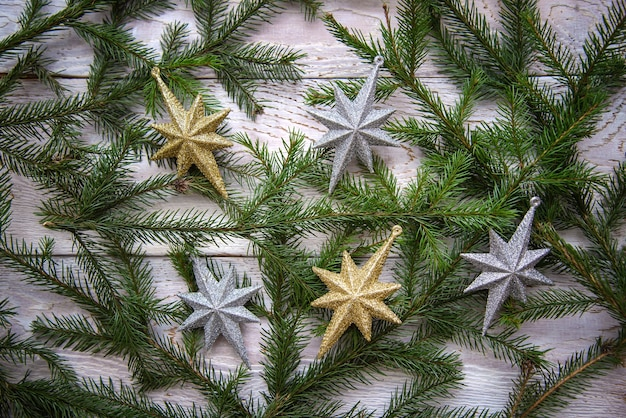 Branches d'arbres de noël et étoiles sur fond de bois blanc