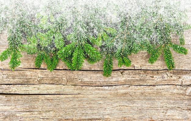 Branches d'arbres de noël sur fond en bois avec effet neige. photo de style vintage