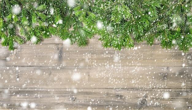 Branches d'arbres de noël sur fond de bois rustique avec effet de chute de neige